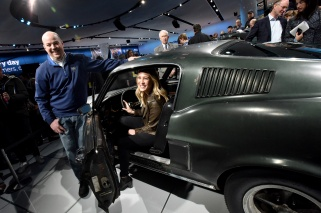 """Sean Kiernan shows his 1968 Mustang GT to Molly McQueen, granddaughter of film legend Steve McQueen. Kiernan's car was used during filming of the movie """"Bullitt."""" Fifty years later, he brought it to the 2018 North American International Auto Show as Ford was revealing its all-new 2019 Mustang BULLITT."""